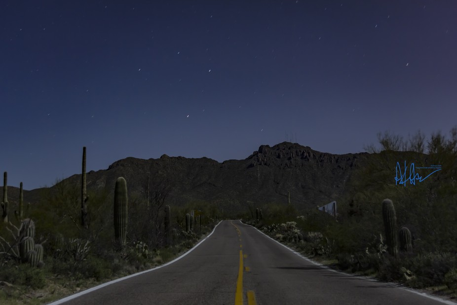 A lonely road to the mountains on a summer night in the desert.