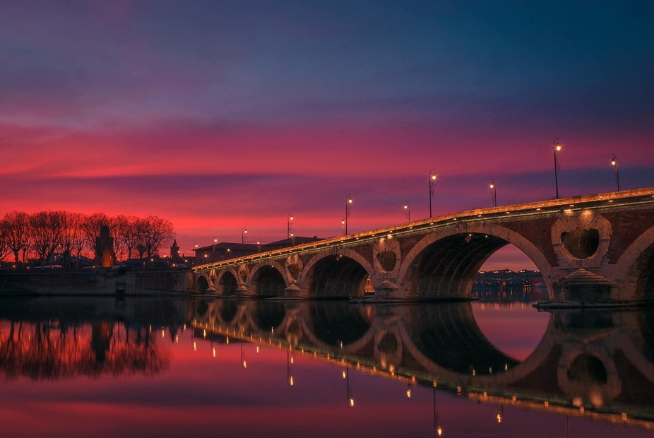 A colourful sky at the end of the day at Pont Neuf which spans the River Garonne in Toulouse, Fra...