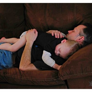 Father and son asleep on the couch.