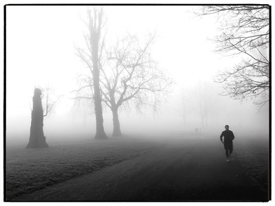 Solitary jogger in Roundwood Park in black and white