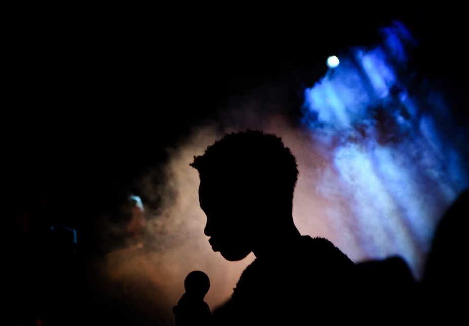 silhouette raising from the shadow formed by the negative space of an african woman holding a mike in an event