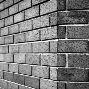 A brick wall, once robbed of it's red colour becoming a contrast in textures and shading.
