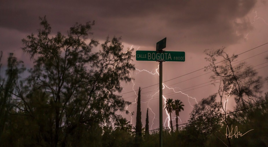 A street sign fronts a powerful lightning strike in the background