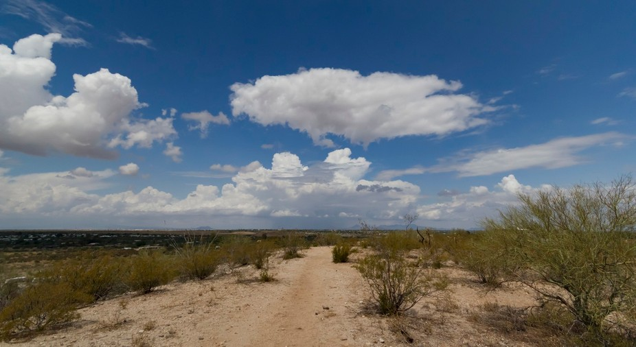 A typical summer monsoon storm cell in the distance with blue skies surrounding the event