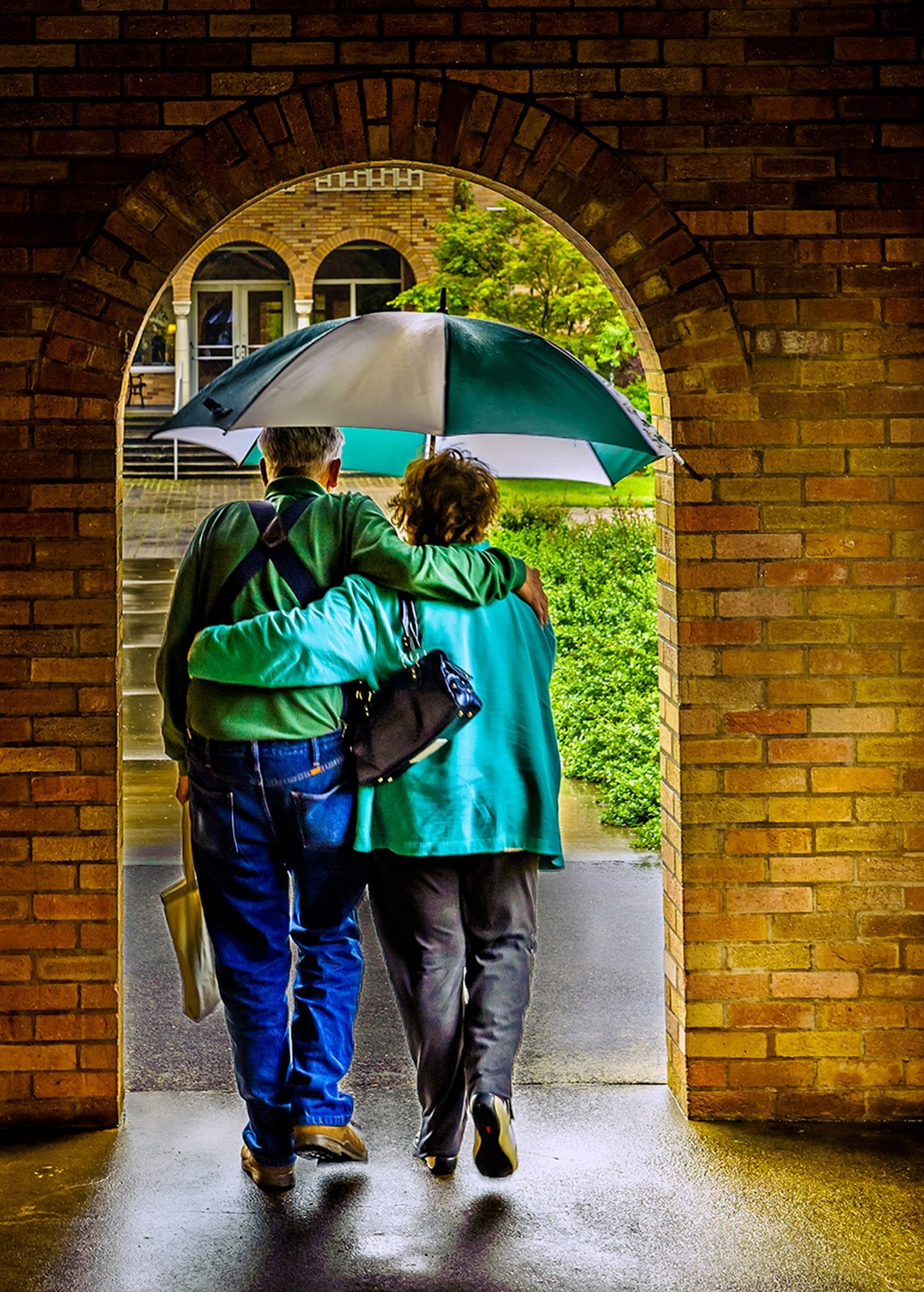 It was captured on a very rainy day at a monastery in Mount Angel, Oregon. It was a rainy day and I love the romantic hug of the older couple as they exited the sheltered walkway into the rain. It was photographed using a Nikon D700 ISO 400, f8 150 of a second. A Nikkor 24-70 f2.8 lens was used at 55mm.