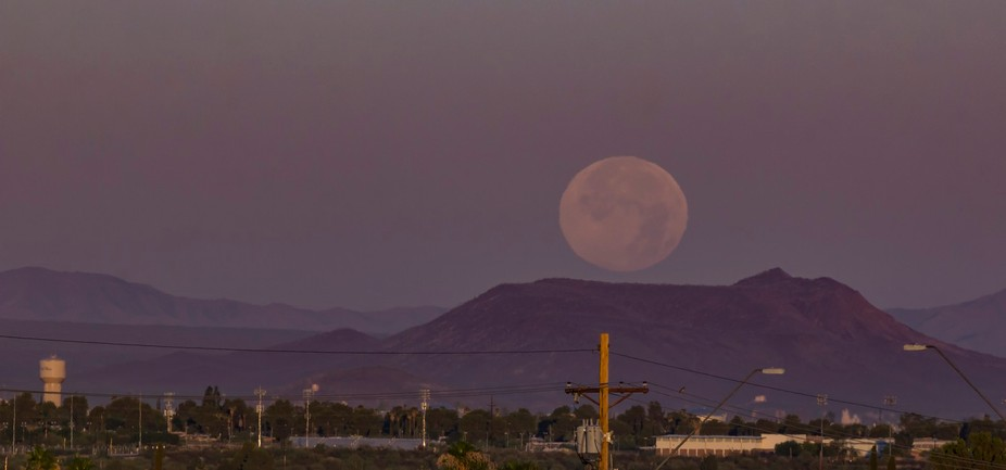 Over the desert city of Tucson the super moon sets in the early morning hours as the sun just rises.