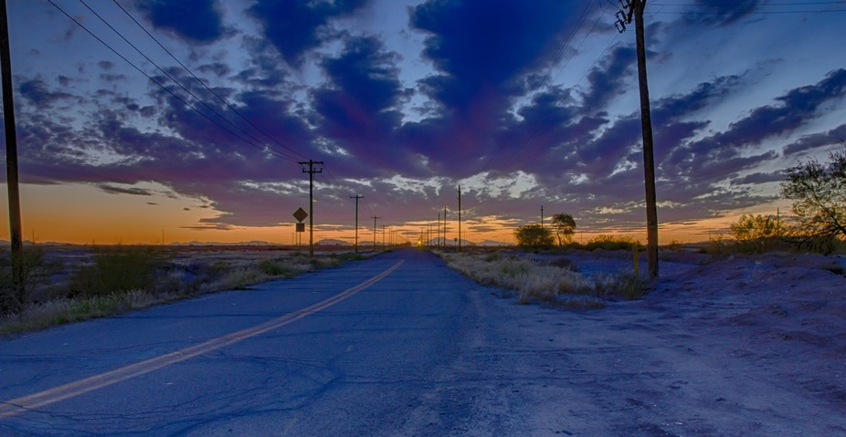 Looking down a road along with telephone/power lines to infinity during an amazing sunset