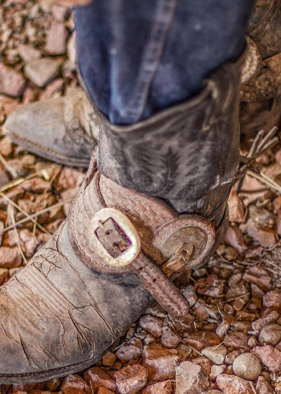 Real cowboy shows his worn boots and the spurs he wears.