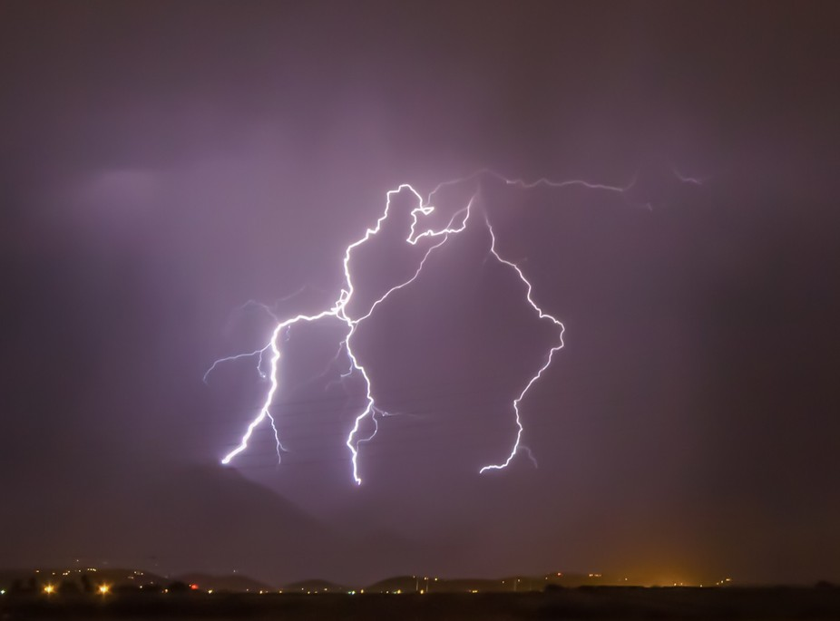 """Powerful lightning as the """"Purple Rain' showers down. The magenta-purple color is natural and caused by the lightning creating plasma to glow."""