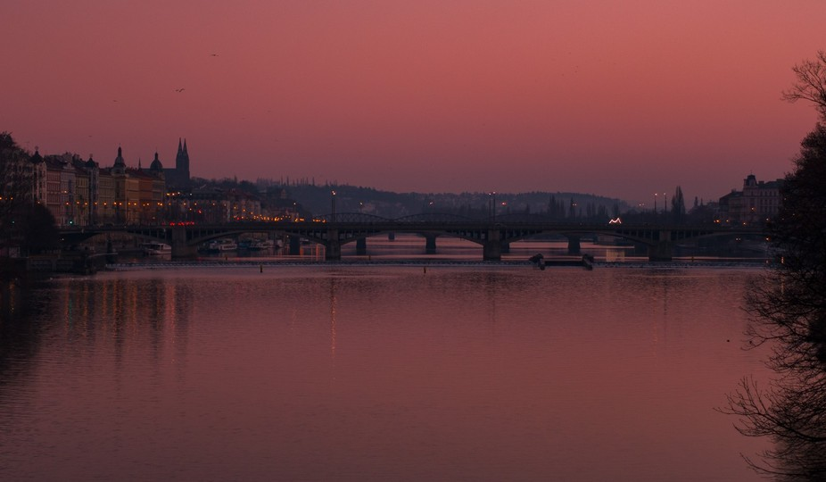 Prague early evening looking down the river a the bridges under a red sky