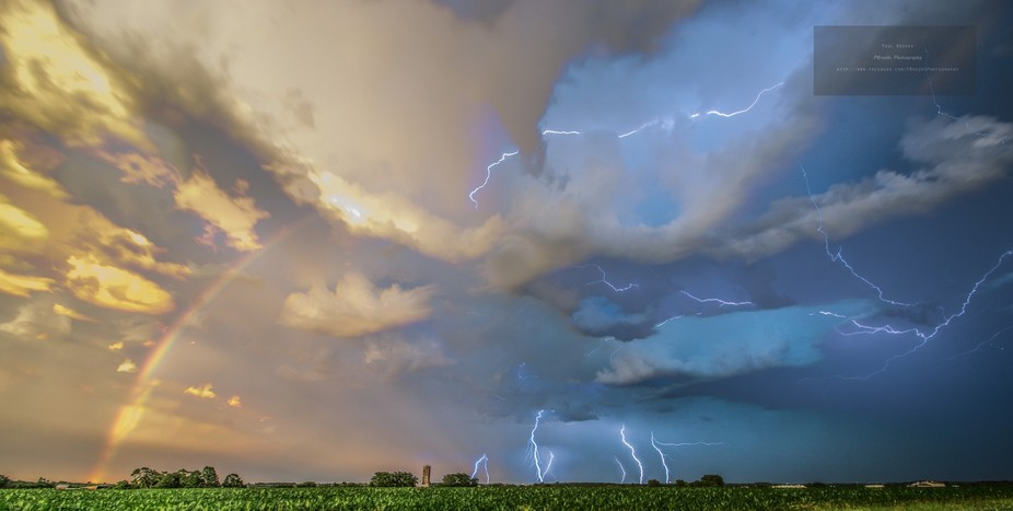 The setting sun illuminates a field and farmstead , as a storm rages overhead and creates this im...