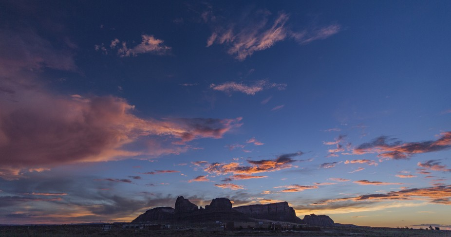 Sundown facing west of Monument Valley with powerful colors in the scattered clouds.