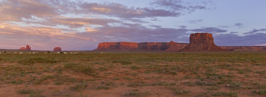 A panorama shot of the outside of Monument Valley at sunset.