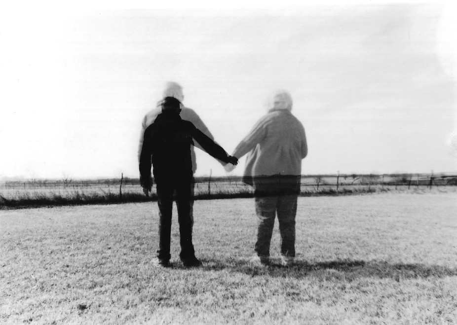 This photo represents grief.  A husband reaches out to hold the hand of his wife, looking over, h...