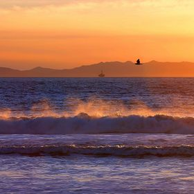 View of the sunset reflecting on the spray from waves breaking on the beach at the end of Seaward Ave. in Ventura, California.