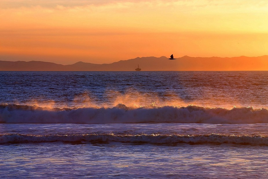 View of the sunset reflecting on the spray from waves breaking on the beach at the end of Seaward...