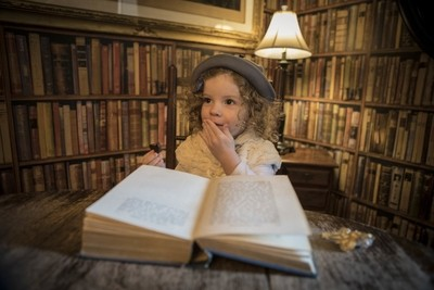 Girl sitting reading vintage library book