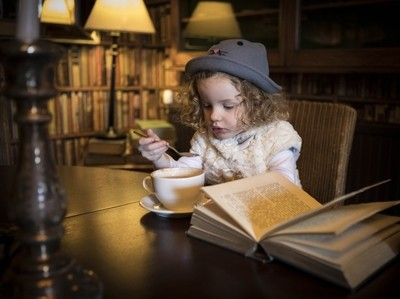 Girl in library reading a children's book
