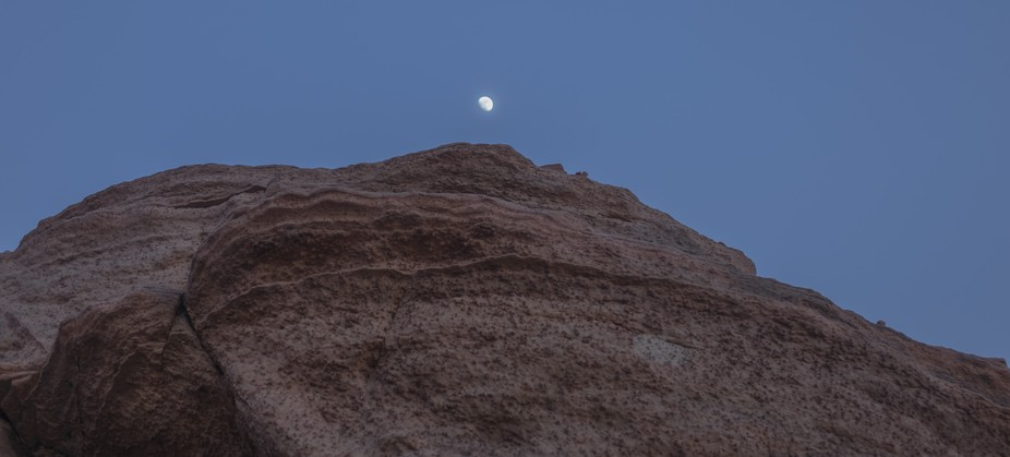 THe moon at dusk over some red rock cliffs