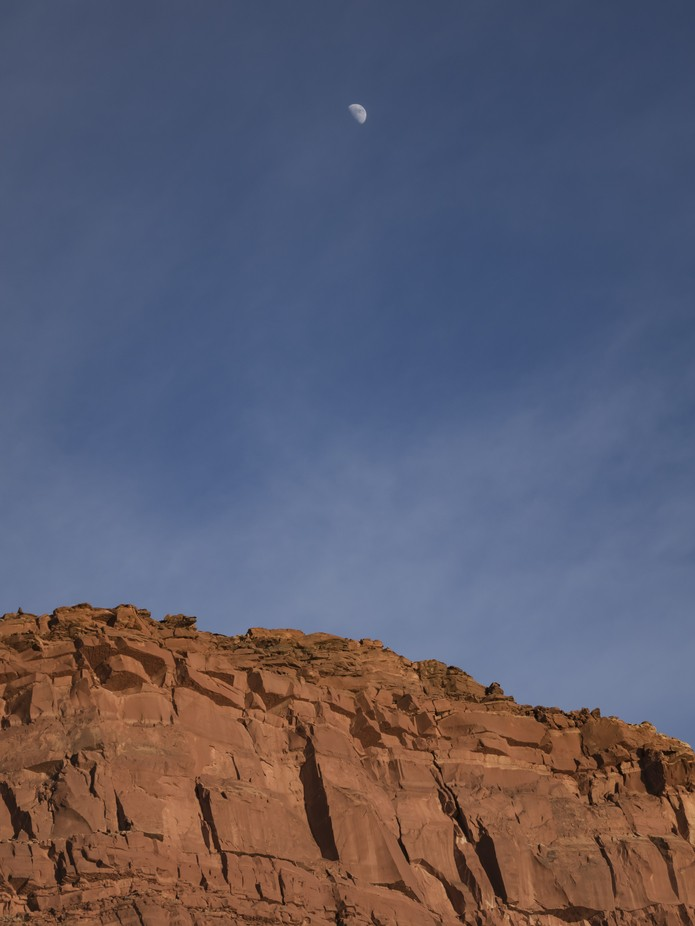 COlors define the sky from the red rock cliff with a half moon in the late afternoon.
