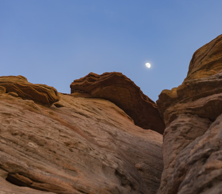 a rock formation seems to hold the dusk moon in place