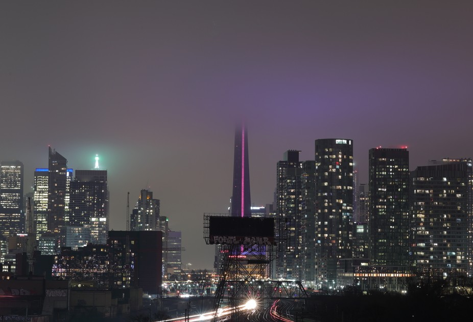 Toronto's skyline on a foggy night as passing trains go in and out of the city