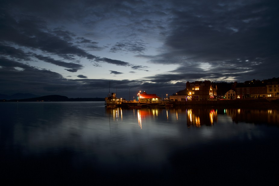 Midnight in Oban, west coast of Scotland. Plenty of people walking on the promenade right outside...