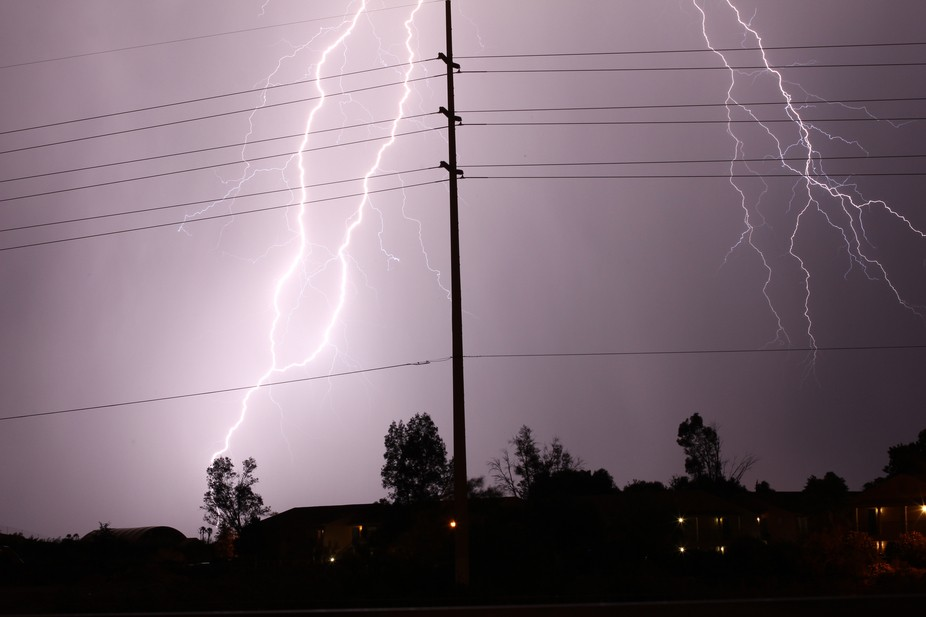Powerful lightning striking down behind high voltage power lines makes for an interesting composition