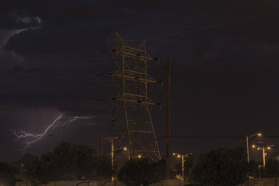 Night time sheet lightning behind a power transmission tower