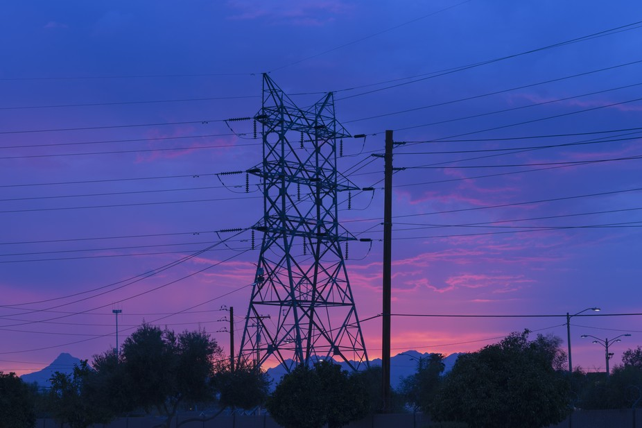 The sunset colors behind a power transmission tower before the oncoming storm.