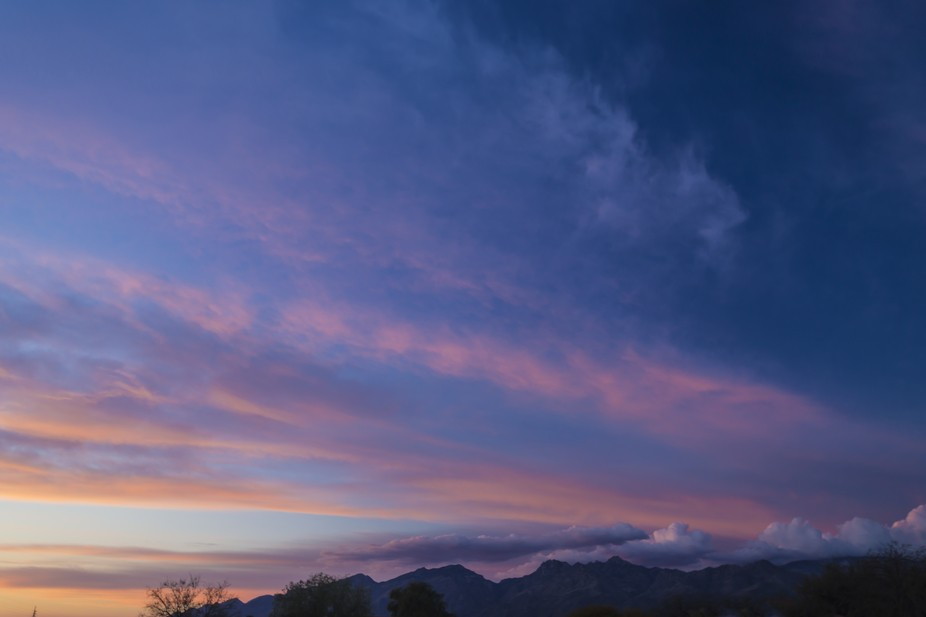The streaks of sunset colors over mountains at dusk