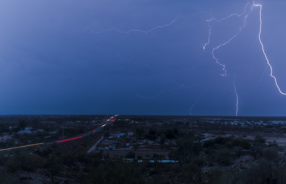 A powerful and extremely large lightning discharge over the desert lights up the sky at night.