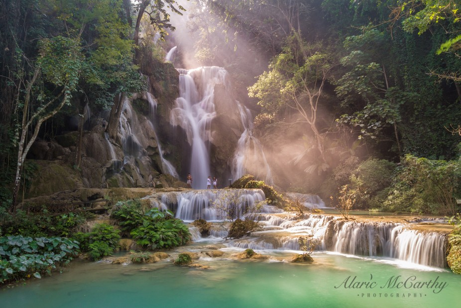 Light rays illuminate the turquoise mineral -rich waters of the Kuang Si falls in Laos