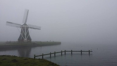 Windmill at foggy lake