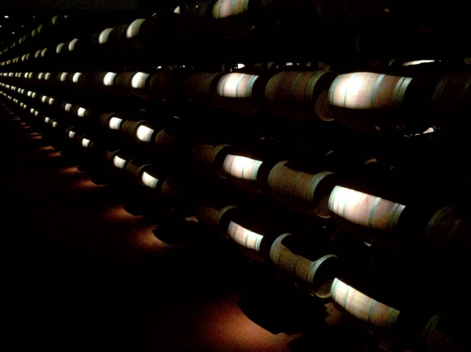 Sparse lighting in the barrel room of a Spanish winery creates an air of mystery and romance.