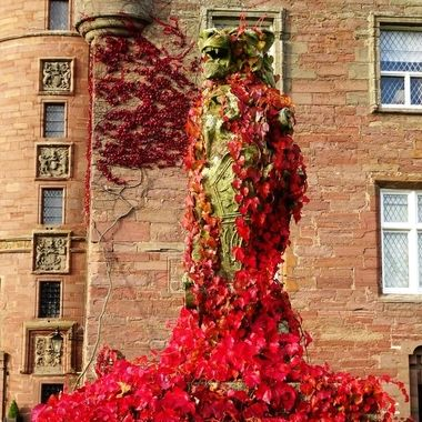 Lion Statue in front of Glamis Castle proudly showing off an Autumn coat of virginia creeper