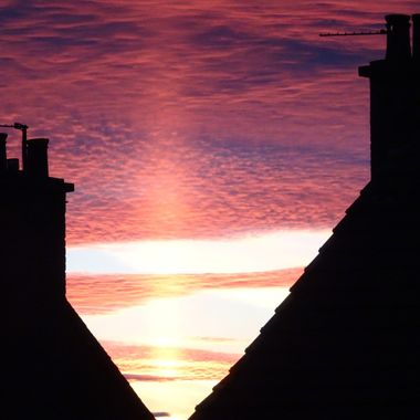 On a lovely evening a brilliant colourful sunset between houses creating  an unusual silhouette