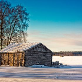 An old barn house and wooden crates unders the bright winter sun on the fields of the Northern Finland.  | TheTravelPictures.com |