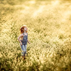 young girl laughing in field of wildflowers