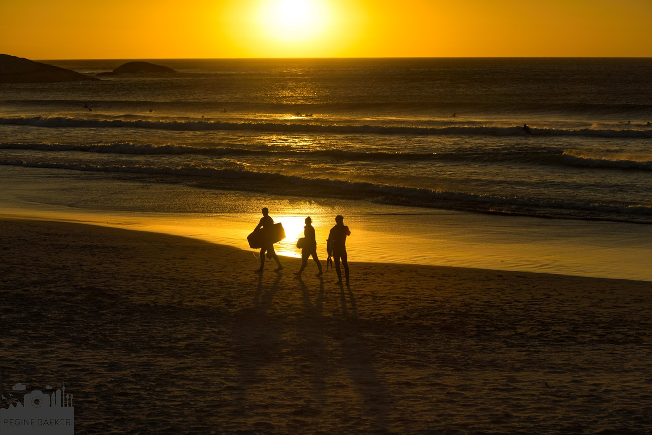 Beach with surfer as silhouettes during sunset-romatic,golden emotions