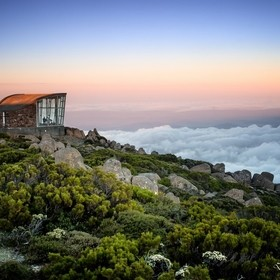 From the top of Mount Wellington in Hobart, Tasmania, Australia, looking down on the clouds with sunset approaching from behind. It was a magnifi...