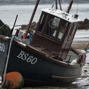 A fishing boat at Low Tide in Rhos on Sea harbour.