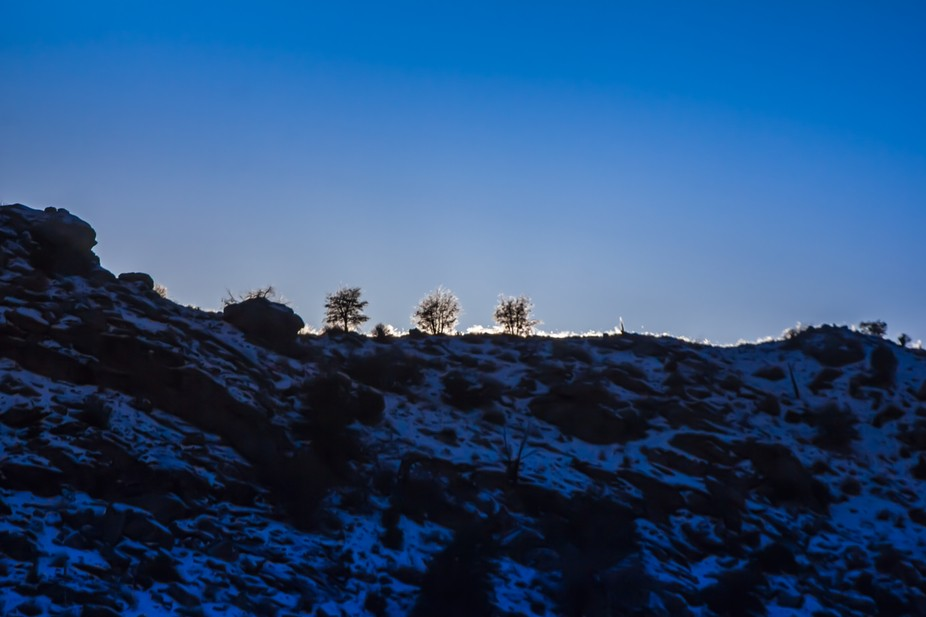 Winter time sunset causes a halo effect over a ridge in desert mountains layered with snow