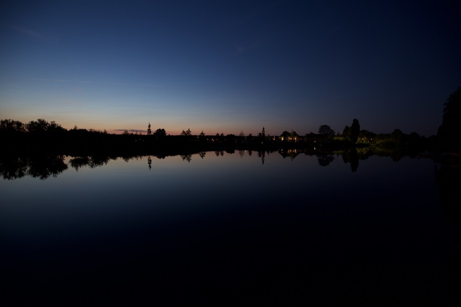 Summer evening on river. The night sky and colors of the fading sunset rejected on the mirrored w...