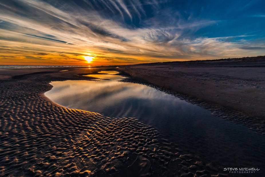 Ripples in the sand and reflective tidal pools during sunset at Robert Moses Beach, Fire Island, NY.