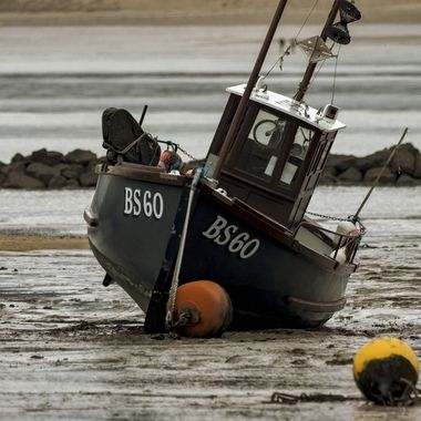 A fishing boat comfortably at rest awaiting the next tide.