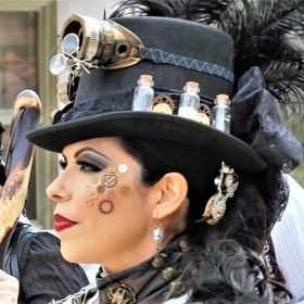 Attractive Steampunk Lady in all her finery.  Her hat, goggles, makeup and mechanical gears say it all