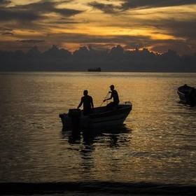 Fishermen go to work at sunset. They will return at dawn, their boat loaded with fish.