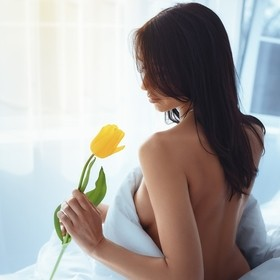 young girl with yellow tulip in the morning