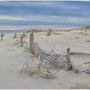 Cold walk on the beach after many storms this season; most of the storm/dune fence had been destroyed; thought the remaining furl - the ocean in the background and the color of the sky softened the cold of the day and the destruction of the winter.